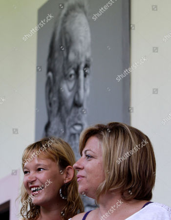 Members of the Spanish Socialist Workers' Party, PSOE, Organizing Secretary Leire Pajin, left, and Secretary of International Policy and Cooperation Elena Valenciano, attend a press conference in Havana, Cuba, . In background, a painting of Cuba's leader Fidel Castro