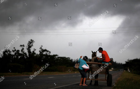 Maria and his father Humberto Rodriguez unload their belongings before the approaching of Hurricane Paula in San Cristobal, Cuba
