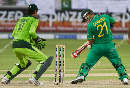 South Africa's JP Duminy, right, lets a ball slip through while Pakistan's wicketkeeper Zulqarnain Haider looks, during their 4th One day international cricket match in Dubai, UAE