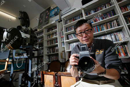 """Stock Photo of Andrew Lau On, Hong Kong director Andrew Lau poses with his camera during an interview with The Associated Press in Hong Kong. Lau said he's shed the baggage of his hit crime thriller """"Infernal Affairs"""" which was remade by Martin Scorsese, as he prepares to release a new kung fu blockbuster starring Donnie Yen"""