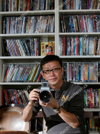 """Andrew Lau On, Hong Kong director Andrew Lau poses with his camera during an interview with The Associated Press in Hong Kong. Lau said he's shed the baggage of his hit crime thriller """"Infernal Affairs"""" which was remade by Martin Scorsese, as he prepares to release a new kung fu blockbuster starring Donnie Yen"""