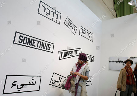 """Stock Image of Visitors look at """"Something Turned Into AThing"""" by US artist Lawrence Weiner displayed at the Grand Palais in Paris, during the Paris FIAC, International Contemporary Art Fair, which runs from Oct. 21 to 24, 2010"""