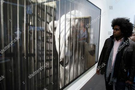 "Alexandre Arrechea Cuban Artist Alexandre Arrechea, at right, looks at ""Homage To Robert Bresson's au hasard Balthazar, Polar Bear"" by US Artist Robert Longo in Paris, France, during the Paris FIAC, International Contemporary Art Fair, which runs from Oct. 21 to 24, 2010"