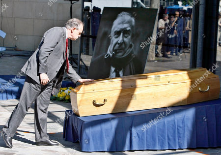 Frederic Mitterrand French Minister of Culture Frederic Mitterrand touches the coffin of French director Claude Chabrol during a public homage at the Cinematheque Francaise in Paris . Chabrol, one of the founders of the New Wave movement whose films probed the latent malice beneath the placid surface of bourgeois life died Sunday Sept. 12, 2010 at the age of 80