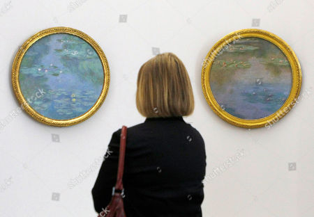 """A visitor looks at the Monet painting """" l'envolee des Nympheas"""" (1908), left, and """"Nympheas"""" (1907) at the Grand Palais Museum in Paris, . The museum presents the first restrospective of the works of Claude Monet (1840-1926)in thirty years . The exhibit, composed of some 200 painings, will be open to the public from Sept. 22 to Jan 24"""
