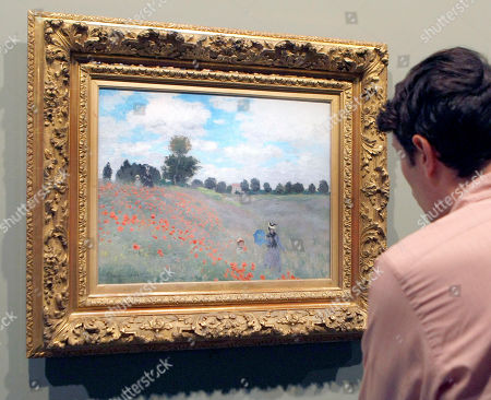 """Stock Image of A visitor looks at the Monet painting """" Les Coquelicots a Argenteuil"""" (1873) """"Poppies at Argenteuil"""" at the Grand Palais Museum in Paris, . The museum presents the first restrospective for thirty years of Claude Monet's works (1840-1926). The exhibit, composed of some 200 paintings, will be open to the public from Sept. 22 to Jan 24"""