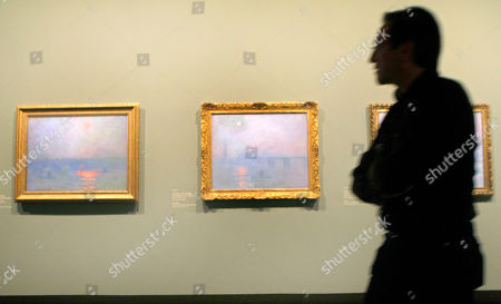 """A visitor walks past """"Waterloo Bridge, Sun in the Fog"""" (1903), left, and """"Charing Cross Bridge, Fog on the Thames"""" (1903) by Claude Monet at the Grand Palais Museum in Paris, . The exhibit, composed of some 200 paintings, is the first retrospective in thirty years of Claude Monet and will be open to the public from Sept. 22 to Jan. 24"""