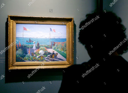 """A visitor looks at the Monet painting """" Terrasse a Sainte-Adresse"""" (1867) at the Grand Palais Museum in Paris, . The museum presents the first retrospective for thirty years of Claude Monet's works (1840-1926). The exhibit, composed of some 200 paintings, will be open to the public from Sept. 22 to Jan 24"""