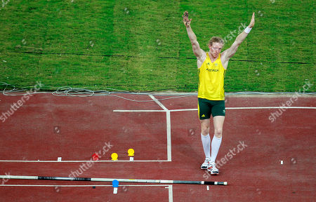 Australia's Steve Hooker waves to the crowd as he stands net to his pole after deciding not to pursue beating the Commonwealth Games record and winning the gold medal in the pole vault final during the Commonwealth Games at the Jawaharhal Nehru Stadium in New Delhi, India