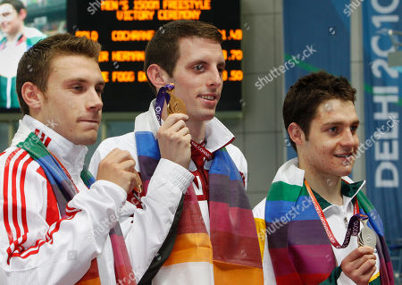 Canada's gold medalist Ryan Cochrane, center, South Africa's silver medalist Heerden Herman, right, and England's bronze medalist Daniel Fogg pose with their medals in the men's 1500m freestyle final during the Commonwealth Games at the Dr. S.P. Mukherjee Aquatics Center in New Delhi, India