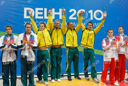 Australian gold medalist in the 4x100 medley relay Eamon Sullivan, Brenton Rickard, Geoff Huegill, and Ashley Delaney celebrate on the podium during the Commonwealth Games at the Dr. S.P. Mukherjee Aquatics Center in New Delhi, India
