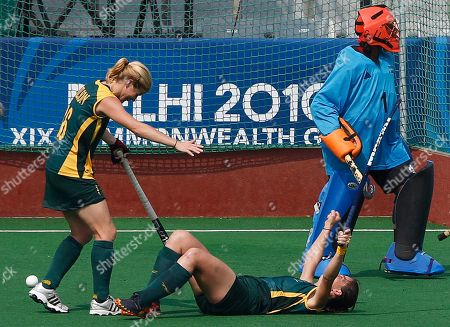 South Africa's Dirkie Chamberlain, on ground, celebrates with teammate Jennifer Wilson after scoring a goal, as Trinidad and Tobago's goalkeeper Petel Derry looks on during their women's field hockey match in the Commonwealth Games at the Major Dhyan Chand National Stadium in New Delhi, India