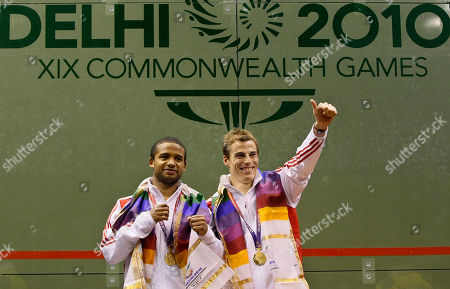 England's Adrian Grant, left, and Nick Mathew display their gold medals after the men's doubles squash match during the Commonwealth Games at the Siri Fort Sports Complex in New Delhi, India
