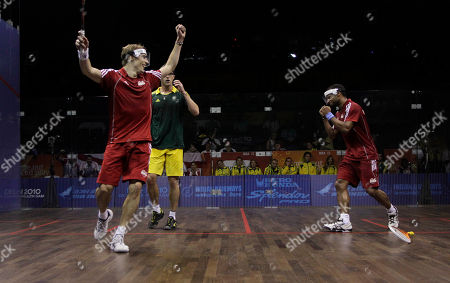 England's Adrian Grant, right, and Nick Matthew celebrate their gold medal victory over Australia in the men's double squash match during the Commonwealth Games at the Siri Fort Sports Complex in New Delhi, India