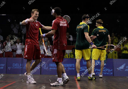 England's Adrian Grant, second left, and Nick Matthew, left, celebrate their gold medal victory over Australia's Stewart Boswell and David Palmer in the men's double squash match during the Commonwealth Games at the Siri Fort Sports Complex in New Delhi, India