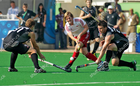 New Zealand's Steve Edwards, left and Shea Mc Aleese, right try to block an advance by England's Ashley Jackson, center, in their men's filed hockey bronze medal match during the Commonwealth Games at Major Dhyan Chand Stadium in New Delhi, India