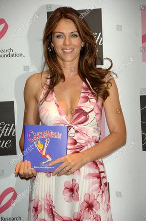 Elizabeth Hurley with the book Cancer Vixen written by cancer survivor Marisa Acocella Marchetto.