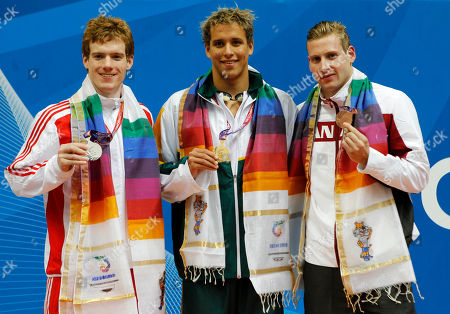 Stock Image of South Africa's Chad Le Clos, center, England's Michael Rock, left, and Canada's Stefan Hirniak, right, pose with their medals for the Men's 200m Butterfly during the Commonwealth Games at the Dr. S.P. Mukherjee Aquatics Stadium in New Delhi, India, . Le Clos won gold, Rock silver and Hirniak bronze