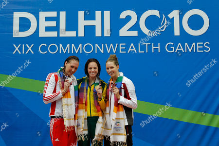 Stock Photo of Gold medalist Emily Seebohm of Australia, center, silver medalist Gemma Spofforth of England, and bronze medalist Julia Wilkinson of Canada, show their medals as they pose on the podium following the 100 m backstroke at the Commonwealth Games in New Delhi, India