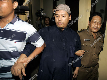 Stock Photo of Mohammed Sofyan Tsauri, who is accused of involvement in plots targeting foreigners and Western embassies in the country, is escorted by plainclothes police officers to his first trial, in a district court in Depok, Indonesia. The former police officer said he helped al-Qaida train 170 members of new terror network in westernmost Aceh province soon after he left the police force