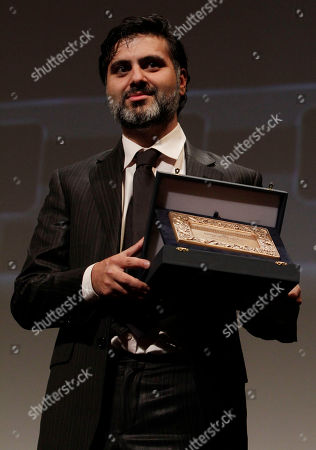 """Hossein Keshavarz Iranian producer Hossein Keshavarz holds the special plaque of the Italian President for the movie which best emphasizes human and social values for the movie """"Dog Sweat"""" during the awarding ceremony at the Rome Film Festival in Rome"""