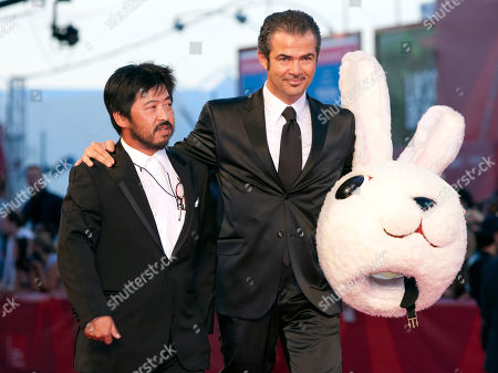 Takashi Shimizu Director Takashi Shimizu, left, flanked by an unidentified guest, is shown after removing a giant mock rabbit head as he arrives for the screening of the film Barney's Version at the 67th edition of the Venice Film Festival in Venice, Italy