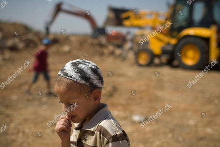 A Jewish settler boy stands next to earth-moving equipment working at a construction site in the West Bank Jewish settlement of Ariel, . Senior Palestinian official Yasser Abed Rabbo said Monday that President Mahmoud Abbas remains ready to walk out on Mideast peace talks if Israel resumes construction in its West Bank settlements now that building restrictions have expired
