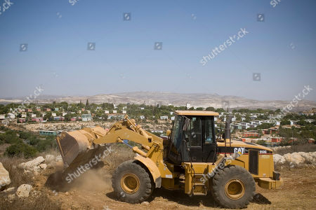 Earth-moving equipment works at a construction site in the West Bank Jewish settlement of Ariel, . Senior Palestinian official Yasser Abed Rabbo said Monday that President Mahmoud Abbas remains ready to walk out on Mideast peace talks if Israel resumes construction in its West Bank settlements now that building restrictions have expired