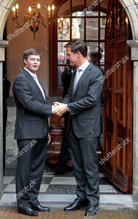 New Prime Minister Mark Rutte, right, bids farewell to outgoing Prime Minister Jan Peter Balkenende, left, in The Hague, Netherlands, . The new right-wing Dutch minority Cabinet was sworn in by Queen Beatrix, ending months of political uncertainty since June elections and usher in a new era of budgetary austerity and a crackdown on immigration