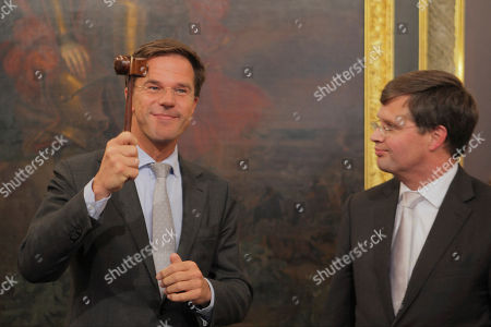 New Prime Minister Mark Rutte, left, holds the gavel after receiving it from outgoing Prime Minister Jan Peter Balkenende, left, in The Hague, Netherlands, . The new right-wing Dutch minority Cabinet was sworn in by Queen Beatrix, ending months of political uncertainty since June elections and usher in a new era of budgetary austerity and a crackdown on immigration