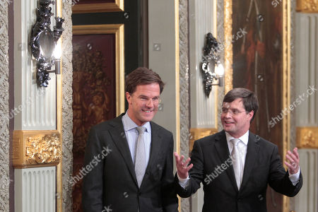 New Prime Minister Mark Rutte, left, and outgoing Prime Minister Jan Peter Balkenende, right, arrive for the of passing of power ceremony in The Hague, Netherlands, . The new right-wing Dutch minority Cabinet was sworn in by Queen Beatrix, ending months of political uncertainty since June elections and usher in a new era of budgetary austerity and a crackdown on immigration
