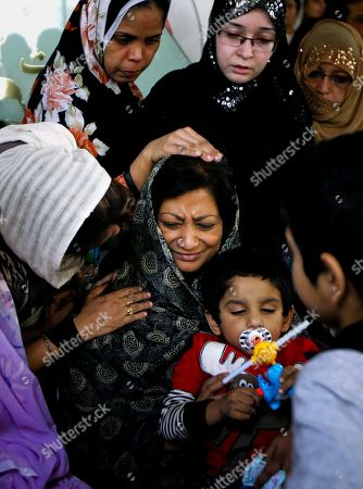 Women comfortShumaila Farooq, center, widow of slain Pakistani politician Imran Farooq, prior to his funeral in Karachi, Pakistan on . Thousands of mourners attended the funeral of Farooq who was stabbed in London in September in a slaying that set off rioting in his hometown of Karachi