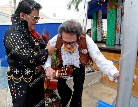 Filipino Elvis Presley impersonator Bodgie Rosas, left, helps fellow impersonator Walter Perez prior to a performance in Manila, Philippines to pay tribute to the King of Rock 'n Roll on his 33rd death anniversary. About 30 impersonators took part in the singing contest with Perez being the oldest contestant at 75 years old