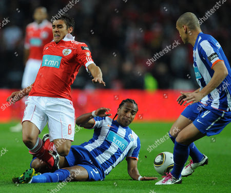FC Porto's Alvaro Pereira, on the pitch, from Uruguay, tackles Benfica's Eduardo Salvio, from Argentina, with Maicon Roque, from Brazil, at right, in a Portuguese League soccer match at the Dragao Stadium in Porto, Portugal