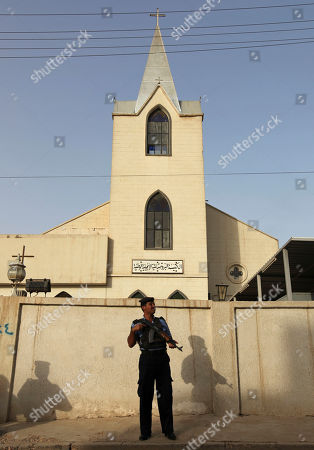 An Iraqi policeman stands guard outside Evangelical Protestant churchin Baghdad, Iraq, . There are fears of a backlash against Christians in predominantly Muslim countries. Canon Andrew White, the chaplain of an Anglican church in Baghdad, said the Iraqi military had warned him that his church had been threatened. Security was beefed up around the Church of Virgin Mary in central Baghdad on Thursday, with military vehicles blocking the entrance to the church and more soldiers were deployed to guard it