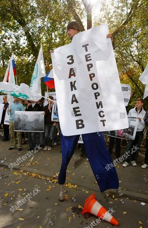 """Activists of the Moscow region Pro-Kremlin movement Mestnye (Locals) hold banners and shout slogans as they protest against Chechen activist Akhmed Zakayevs visit to Poland in front of the Polish Embassy in Moscow, with the poster saying """"Zakayev is a terrorist!"""". Tens of activists of the youth movement """"Mestnye"""" (Locals) gathered Monday near the Polish embassy in Moscow to protest the Polish government's decision to let go Akhmed Zakayev, a Chechen emigre wanted in Russia. Zakayev, one of Russia's most wanted men, was arrested in Poland Friday on Russian charges related to Chechnya's separatist war of the 1990's, but later set free. Zakayev faces charges of murder, kidnapping and terrorism"""