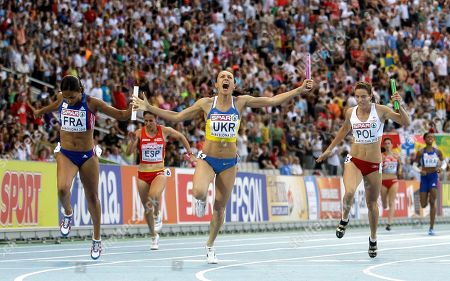 Ukraine's Yelizaveta Bryzhina, center, celebrates as she crosses the finish line ahead of France's Christine Arron, left, and Poland's Weronika Wedler to win the Women's 4x100m final during the European Athletics Championships, in Barcelona, Spain