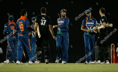 Members of the Indian cricket team congratulate New Zealand batsmen Kyle Mills, center in black, and Andy McKay, right, at the end of the tri-nation series one day international cricket match between India and New Zealand in Dambulla, Sri Lanka, . India beat New Zealand by 105 runs Wednesday to advance to the final of the tri-series also involving Sri Lanka