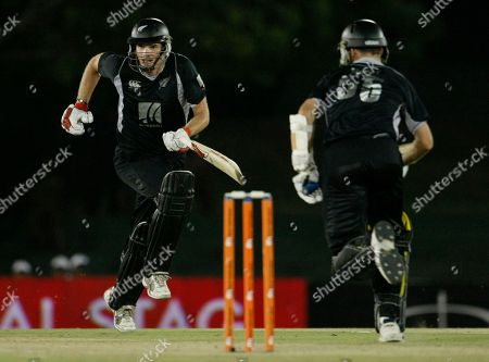 New Zealand's batsmen Kyle Mills, left, and Andy McKay run between wickets during the tri-nation series one day international cricket match between India and New Zealand in Dambulla, Sri Lanka