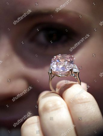 """An employee of Sotheby's auction house holding a 24.78 carat fancy intense pink diamond mounted as a ring, that was last seen on the market some 60 years ago according to the house, ahead of an auction in central London. In November 2010, a rare pink diamond smashed the world record for a jewel at auction, selling for more than $46 million to a well-known gem dealer. London jeweler Laurence Graff paid $46,158,674, for the 24.78-carat """"fancy intense pink"""" diamond, which he immediately named """"The Graff Pink"""