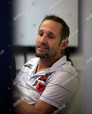 Briton Stuart Scott Crawford, 44, sits in a room after a press conference at the Immigration Police Headquarters in Bangkok on . Crawford allegedly fled to Thailand in 2008 after killing a British friend in Surrey and transferred 6,500 pounds into his own account