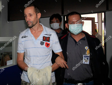A Thai Immigration Police officer escorts Briton Stuart Scott Crawford, 44, after a press conference at the Immigration Police Headquarters in Bangkok on . Crawford allegedly fled to Thailand in 2008 after killing a British friend in Surrey and transferred 6,500 pounds into his own account