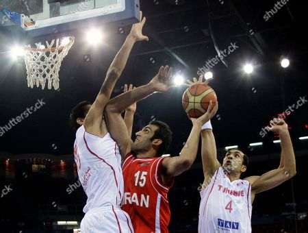 Iran's Hamed Ehadadi goes up for a shot as Tunisia's Radhouane Slimane, right, and Salah Mejri guard, during their World Basketball Championship preliminary round match in Istanbul, Turkey