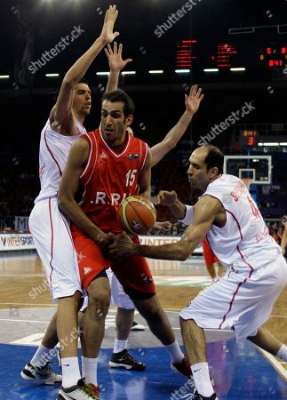 Iran's Hamed Ehadadi, center, fights for the ball against Tunisia's Radhouane Slimane, right, and Salah Mejri during their World Basketball Championship preliminary round match in Istanbul, Turkey