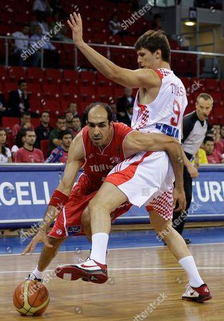 Tunisia's Radhouane Slimane drives past Croatia's Marko Tomas during their World Basketball Championship preliminary round match in Istanbul, Turkey