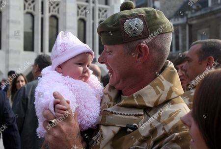 Stock Picture of Welcome home ceremony for soldiers of Somme Company, The London Regiment after their tour of duty in Afghanistan. The troops were greeted by their families  -  Corporal Jason Turner with his 4 month old daughter Shay  The one hundred and forty soldiers, largely members of the Territorial Army from London