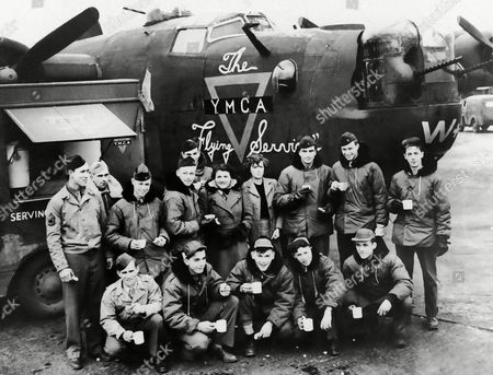 American airmen at a bleak airdrome in East Anglia, England, christened a Liberator bomber, The YMCA Flying Service, to reciprocate for the many visits of the YMCA tea car to their station in an undated photo. After the christening ceremony are, left to right, front row; Corporal Harry L. Worman, Evansville, Ind.; S/Sergeant Gene Farquharson, Los Angeles, Cal.; S/Sergeant John H. Capik, Perth Amboy, N.J.; T/Sergeant. Leo Herzlich, New York City; S/Sergeant Eugene L. Psyk, Rochester, N.Y. Second row, left to right are: T/Sergeant Harold L. Detty, Londonderry, Ohio; Corporal Henry Bradish, Pueblo, Col.; Lieutenant Cleverdon, Indiana; 2nd Lieutenant Edmond L. Kessig, Racine, Wisc.; 2nd Lieutenant Charles D. Gridley, Waban, Mass.; Mrs. R.D. Park, St. Fillans Beetley, Norfolk, England; Miss Mayne, West Lodge; Easton, Norfolk; 2nd Lieutenant James E. Mace, Sheridan, Ind.; 1st Lieutenant Robert H. Solomon, Valley View, Texas; T/Sergeant Hugh E. Moeller, Hasting, Minn
