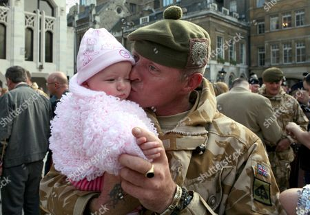 Jason Turner greets his 4-month-old daughter Shay - Welcome home ceremony for soldiers of Somme Company, The London Regiment after their tour of duty in Afghanistan. The  parade was hosted by the Lord Mayor of London and the troops were greeted by their families