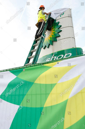 A Greenpeace activist puts up a banner as they block off a British Petroleum fuel station in protest as the BP board announce their annual results, in London, . BP is jettisoning CEO Tony Hayward, whose verbal blunders made the oil giant's image even worse as it struggled to contain the Gulf oil spill, and will assign him to a key job in Russia, a person familiar with the matter said Monday