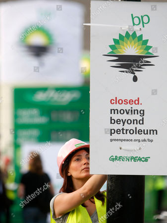 A Greenpeace activist puts up a placard as they block off a British Petroleum petrol station in protest as the BP board announce their annual results, in London, . BP is jettisoning CEO Tony Hayward, whose verbal blunders made the oil giant's image even worse as it struggled to contain the Gulf oil spill, and will assign him to a key job in Russia, a person familiar with the matter said Monday